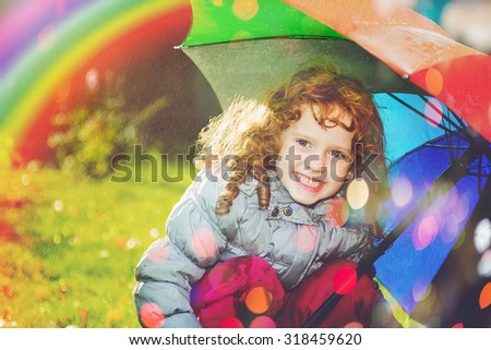 Laughing girl in the rain with a rainbow and with color bokeh.  Happy and healthy childhood concept.