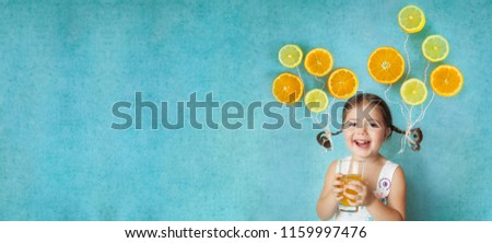 Laughing girl keeps glass of fresh citrus juice with bright balloons (orange and lemon slices) on her pigtails. Healthy food concept. Panoramic banner with copy space