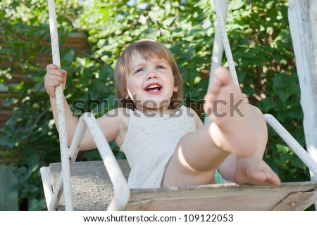Laughing girl on swing in summer park