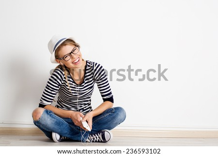 Laughing girl sitting on wooden flooring with smart phone in headset. Music, leisure and technology concept.