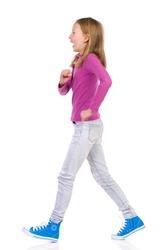 Laughing girl walking. Side view. Full length studio shot isolated on white.