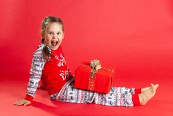laughing girl with two pigtails and in Christmas pajamas sits on the floor and holds a gift box on her lap, isolated on a vibrance background.