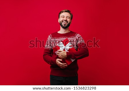 Laughing glad man with beard holding new year present. Studio portrait of white guy enjoying christmas.