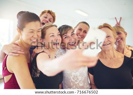 Laughing group of senior women standing arm in arm together taking a selfie with their dance teacher during ballet class