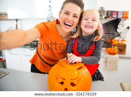 Laughing halloween dressed girl and young mother making selfie with big orange pumpkin Jack-O-Lantern in decorated kitchen. Traditional autumn holiday