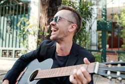 Laughing handsome mature man in sunglasses sitting on pavement in the street, singing song and playing guitar