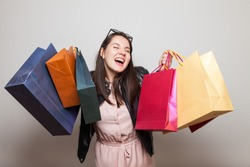 Laughing happu girl holds shopping bags