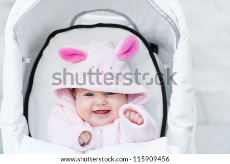 Laughing happy baby girl sitting in a white stroller in a bunny dress-up