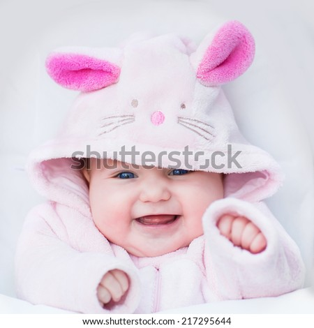 Stock Photo Laughing happy baby girl sitting in a white stroller in a bunny dress-up