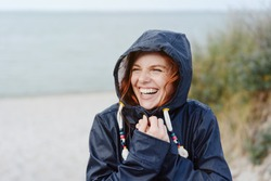 Laughing happy young woman embracing the cold autumn weather snuggling into her warm anorak with a beaming vivacious smile as she strolls along a beach