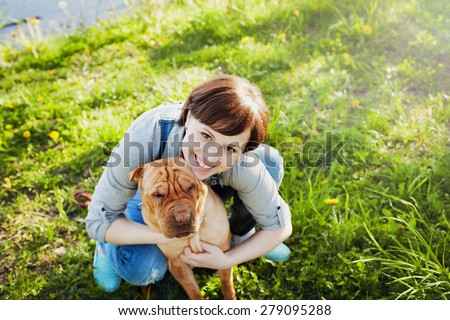 laughing happy young woman in denim overalls hugging her red cute dog Shar Pei in the green grass in sunny day, true friends forever, people pets concept