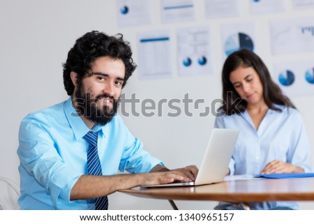 Laughing indian businessman and businesswoman at work at desk at office of company