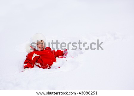 Laughing kid lying in the deep snow