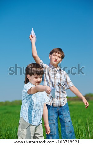 Laughing kids playing with paper planes in summer day - stock photo