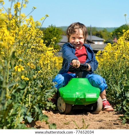 Laughing little boy drives toy car via rapeseed field in bloom