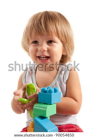 Laughing little boy playing with blocks, isolated on white background