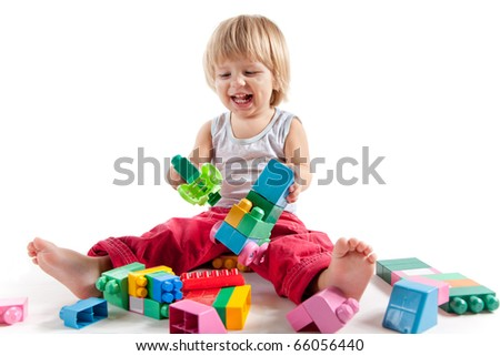 Laughing little boy playing with colorful blocks, isolated on white background