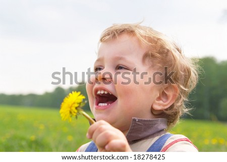 laughing little boy with dandelion in hand