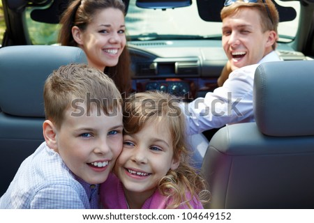 Laughing little brother and sister sit on back seat of open top car, nestling with their cheeks, on front seats - young laughing couple