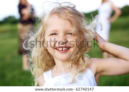 laughing little girl and two woman on background