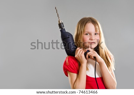Laughing little girl holding electric drill