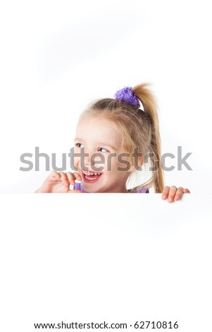 laughing little girl looking over empty board isolated