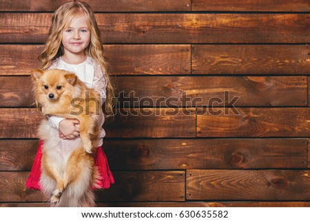 Stock Photo Laughing little girl with long blond hair holds each dog in the background of a wooden wall.Advertising space