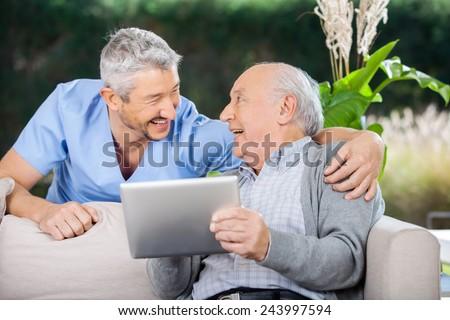Laughing male caretaker and senior man using tablet computer at nursing home porch #243997594