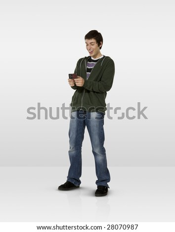 Laughing male teen looking at mobile phone
