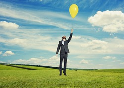 laughing man flying with yellow balloon