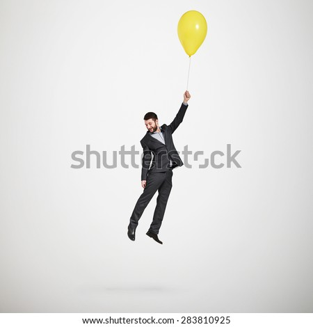 laughing man flying with yellow balloon and looking down over light grey background