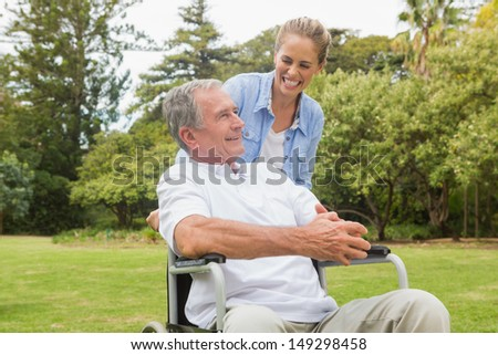 Laughing man in wheelchair and daughter talking on a sunny day in park