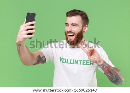 Photo of Laughing man in white volunteer t-shirt isolated on pastel green background. Voluntary free work assistance help charity grace teamwork concept. Doing selfie shot on mobile phone showing victory sign