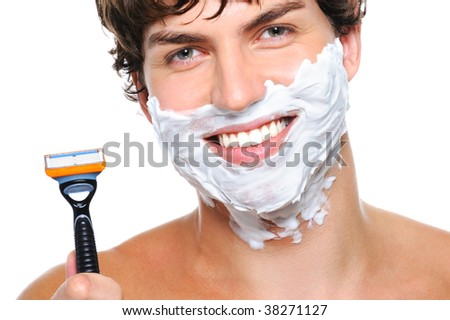 Laughing man's face with shaving cream on it and razor near the face