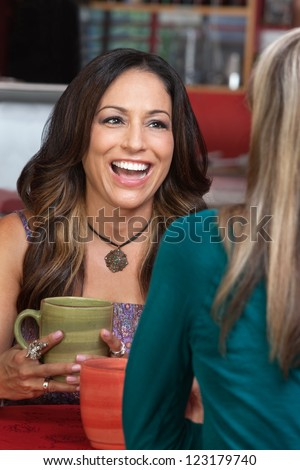 Laughing mature woman with friend in restaurant