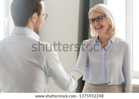 Laughing middle aged lady in glasses standing in office handshake with new employee specialist starting career at company, ceo woman welcome client shake hands express regard, nice to meet you concept