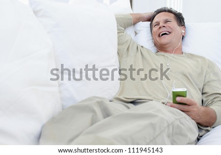 Laughing middle aged man lying on couch while listening music