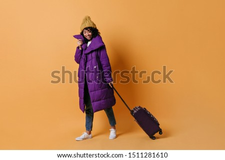 Laughing mixed race woman posing with valise. Full length view of curly girl in down jacket holding suitcase.