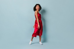 Laughing mixed red woman in white gumshoes looking at camera. Ecstatic girl in red dress standing on blue background.