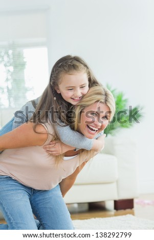 Laughing mother giving daughter a piggy bank in the living room