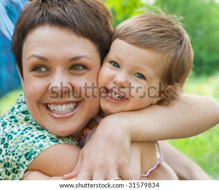 Laughing mother hugs her dearest baby