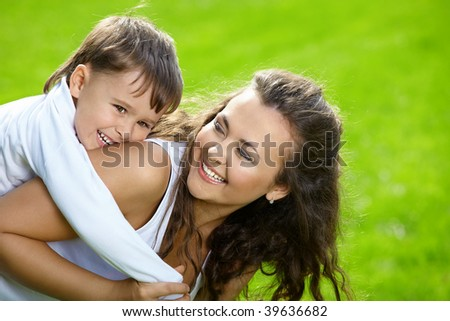 Laughing mum rolls on a back of the small son in park - stock photo