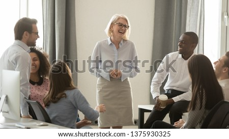 Laughing old coach team leader talking with diverse coworkers chatting at business meeting, friendly multi racial office workers and middle aged woman ceo have fun conversation at coffee break concept