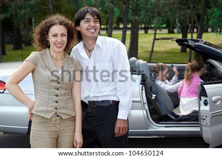 Laughing parents stand near cabriolet, children play in the car