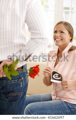 Laughing pregnant woman with ultrasound baby picture in hand getting red rose from man.?