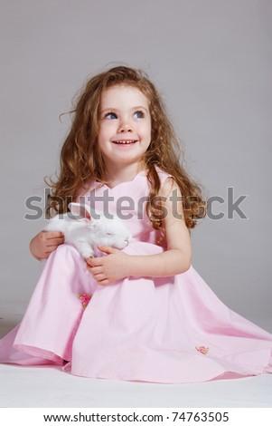 Laughing preschool girl holding white rabbit on knees