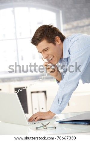Laughing professional man on landline call with laptop computer, looking at screen.?