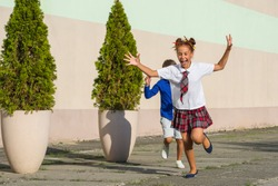 Laughing schoolchildren - a girl and a boy are happily running around the schoolyard