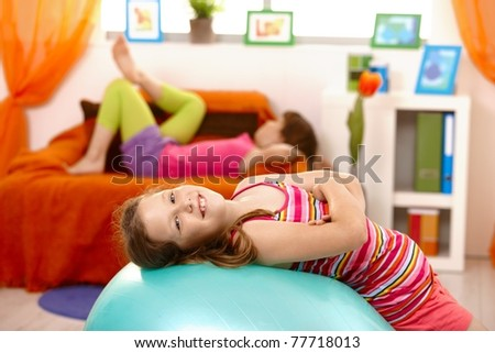 Laughing schoolgirl lying on gym ball, looking at camera, friend lying on sofa in background.?