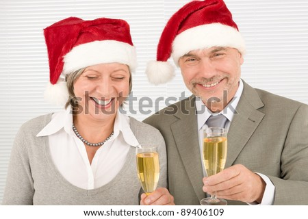 Laughing senior businesspeople in Christmas  Santa hat drink champagne